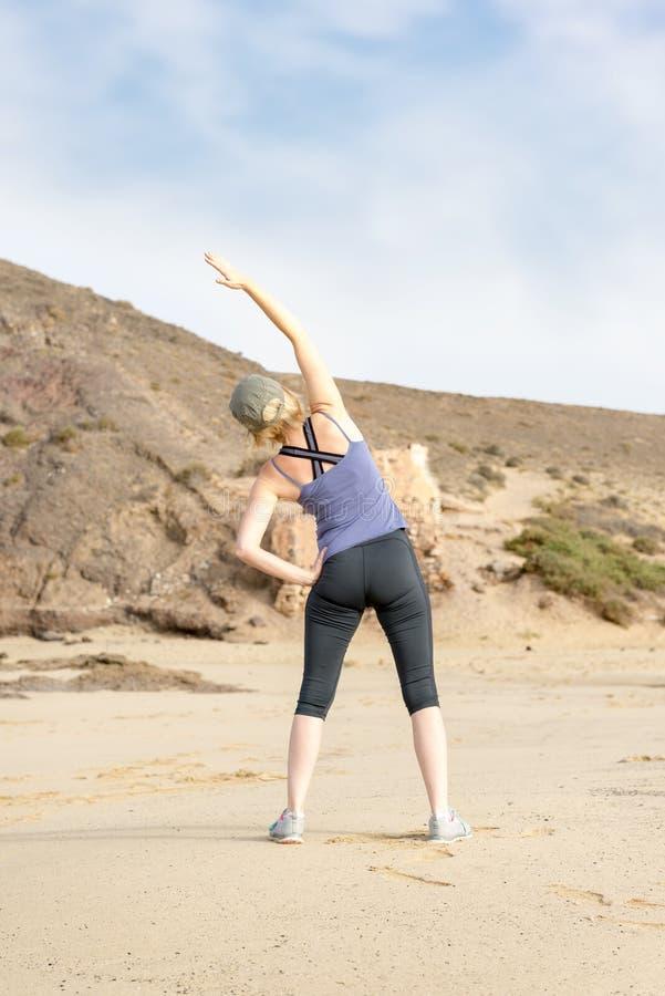 做旁边伸手可及的距离舒展的运动服的妇女 库存图片