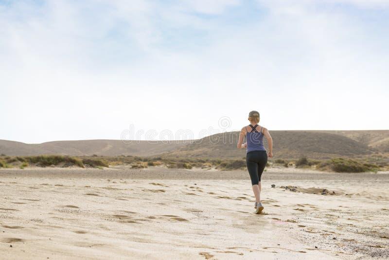 做早晨健身的妇女跑在沙漠 免版税库存图片