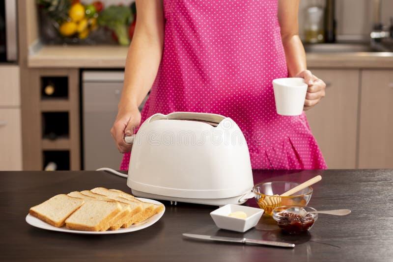 做早餐和喝咖啡的妇女 免版税图库摄影