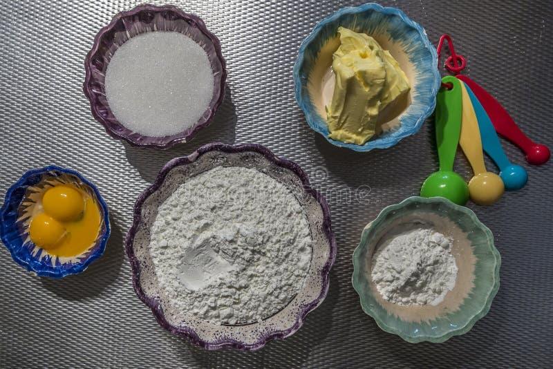 做曲奇饼、玉米淀粉、糖、蛋、玉米淀粉、黄油和量匙匙子的成份的图象 免版税库存图片