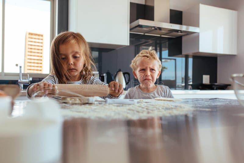 做曲奇饼和男孩的小女孩哭泣在厨房里 免版税图库摄影