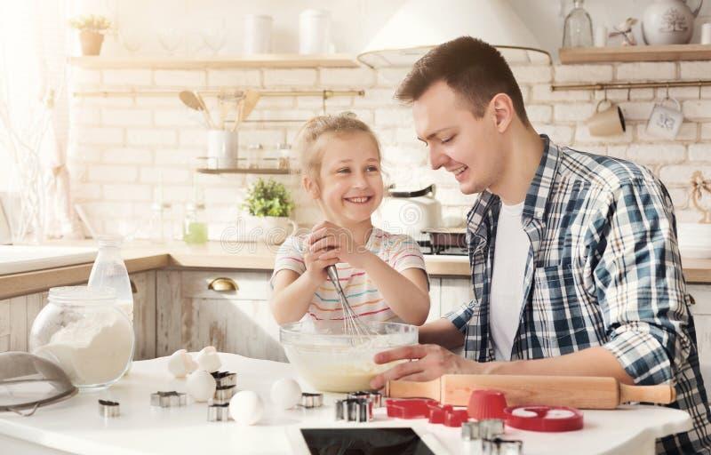 做曲奇饼的父亲和女儿在厨房里 免版税库存图片