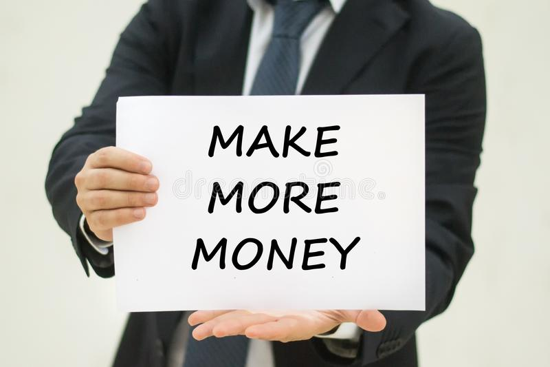 做更多金钱文本在纸 免版税库存照片