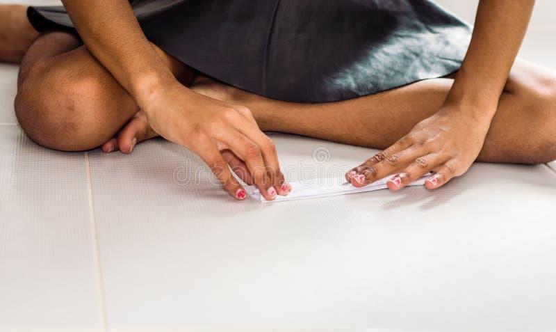 做有白皮书的小黑人女孩origami飞机在地板 免版税库存照片