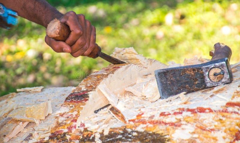 做木头的木匠雕刻创造书刊上的图片 免版税库存照片