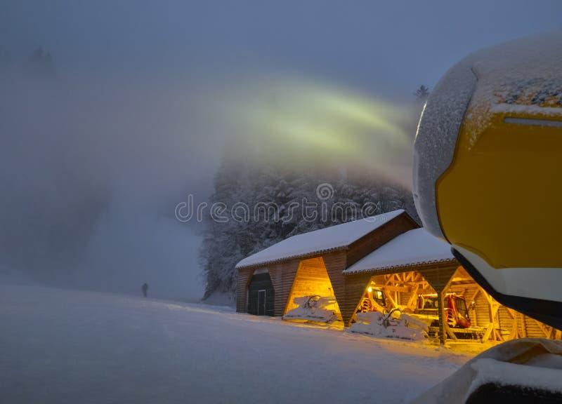 做机器的雪在滑雪倾斜在晚上 图库摄影