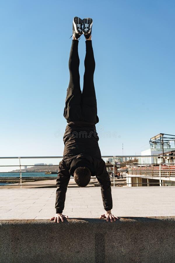 做杂技和站立在他的胳膊的parkour人照片在早晨锻炼期间在海边旁边 免版税库存图片