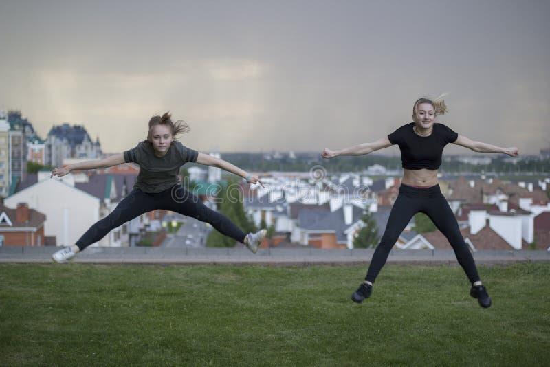 做杂技的两位年轻女性体操运动员跳与在背景的都市风景 免版税库存照片