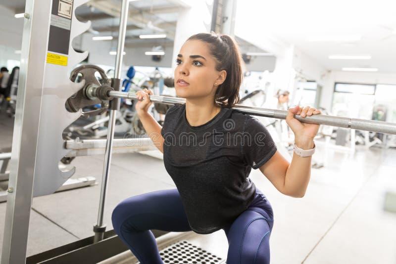 做杠铃的女运动员在健身房蹲 免版税库存图片