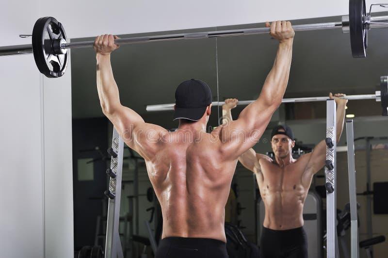 做杠铃肩膀新闻锻炼的英俊的强有力的运动人 免版税图库摄影