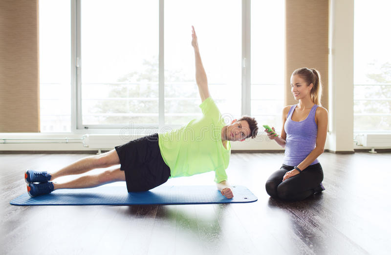 做板条的男人和妇女在健身房的席子行使 图库摄影