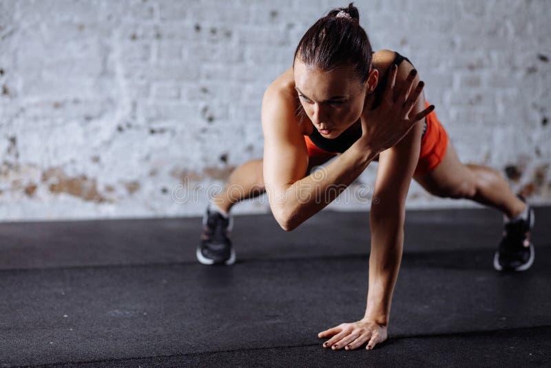 做板条的运动服的美丽的妇女,当trainnig在十字架适合的健身房时 免版税库存图片