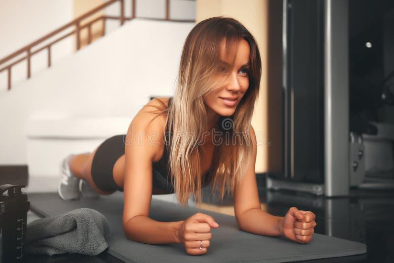 做板条锻炼的亭亭玉立的健身年轻女人运动员女孩在健身房 库存照片