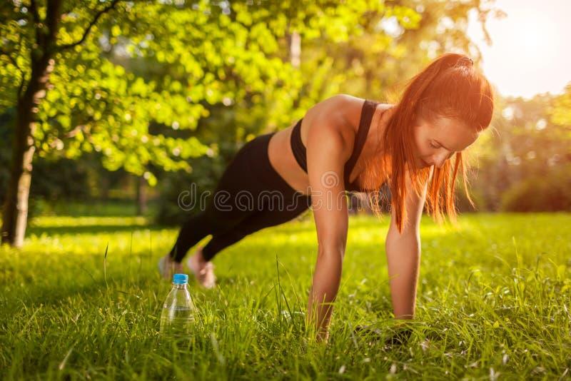 做板条锻炼的嬉戏妇女室外在夏天公园 刺激 健康生活方式 免版税库存照片
