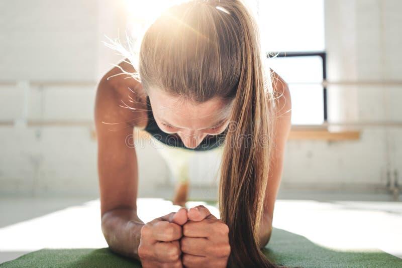 做板条锻炼的适合的少妇改进她的吸收 做crossfit的健身房的女性 免版税图库摄影