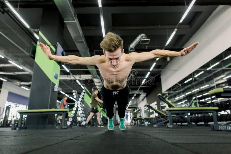 做极端俯卧撑的年轻人运动员作为建身的训练一部分 免版税库存图片