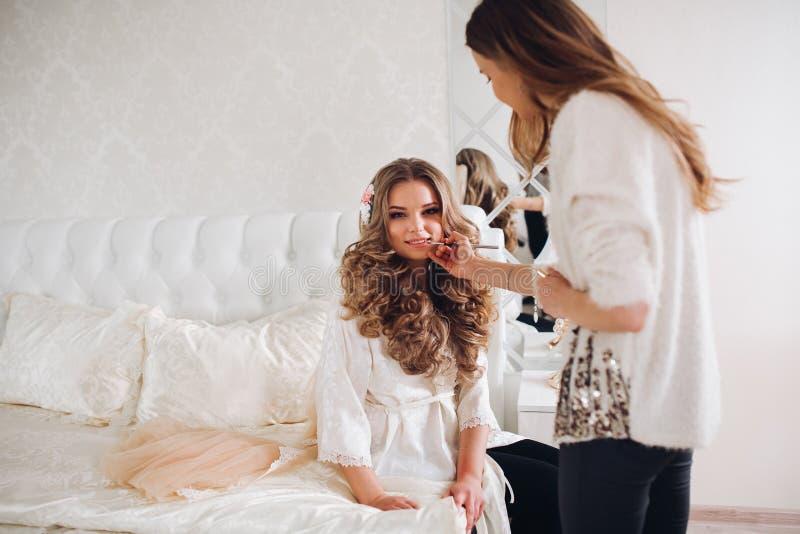 做构成的新娘早晨在屋子里 做专家的化妆师组成少妇 化妆师 免版税库存图片