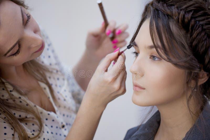 做构成的美丽的年轻女人在一位专业化妆师 库存图片