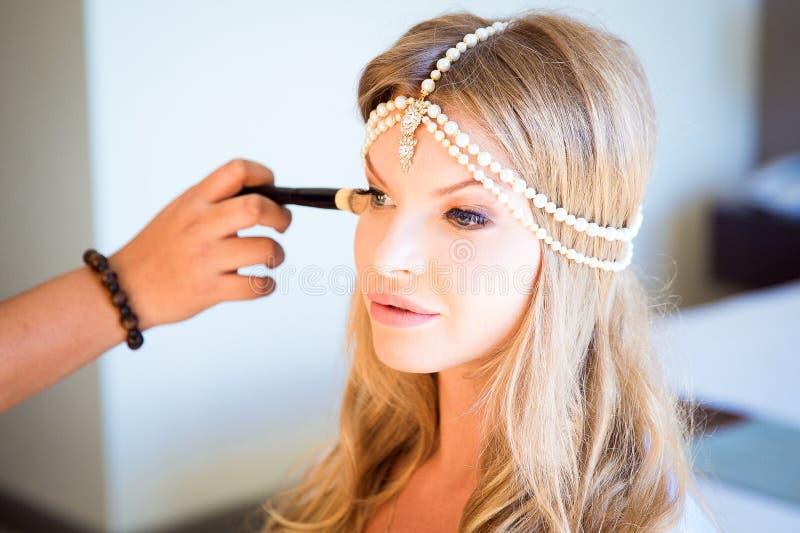 做构成的美丽的白肤金发的新娘在她的婚礼之日在mirro附近 免版税库存图片