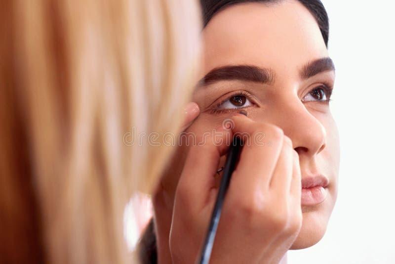 做构成的过程 化妆师与在式样面孔的刷子一起使用 年轻女人画象美容院内部的 免版税库存照片