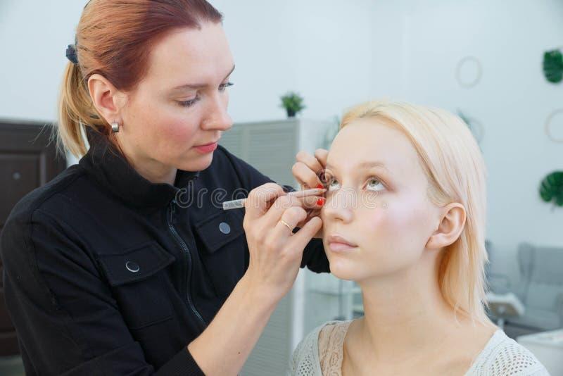 做构成的过程 化妆师与在式样面孔的刷子一起使用 图库摄影