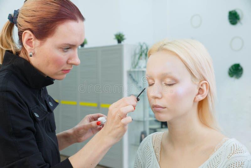做构成的过程 化妆师与在式样面孔的刷子一起使用 免版税图库摄影