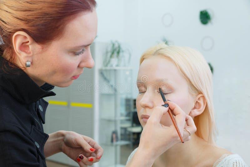 做构成的过程 化妆师与在式样面孔的刷子一起使用 免版税库存照片