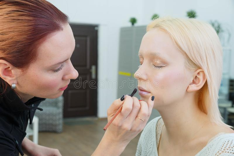 做构成的过程 化妆师与在式样面孔的刷子一起使用 免版税库存图片