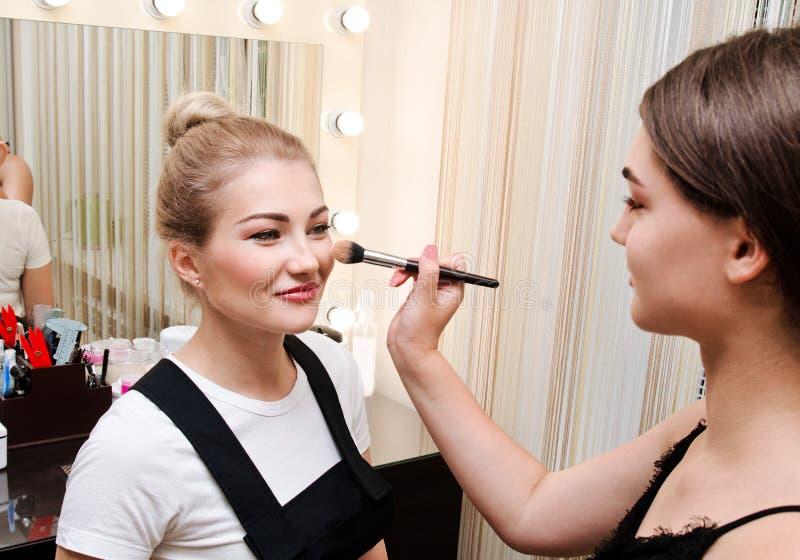 做构成的过程 组成应用眼影膏的艺术家于美丽的年轻女人 免版税库存照片