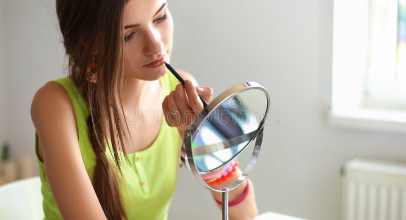 做构成的年轻美丽的妇女在镜子附近,坐在书桌 库存图片
