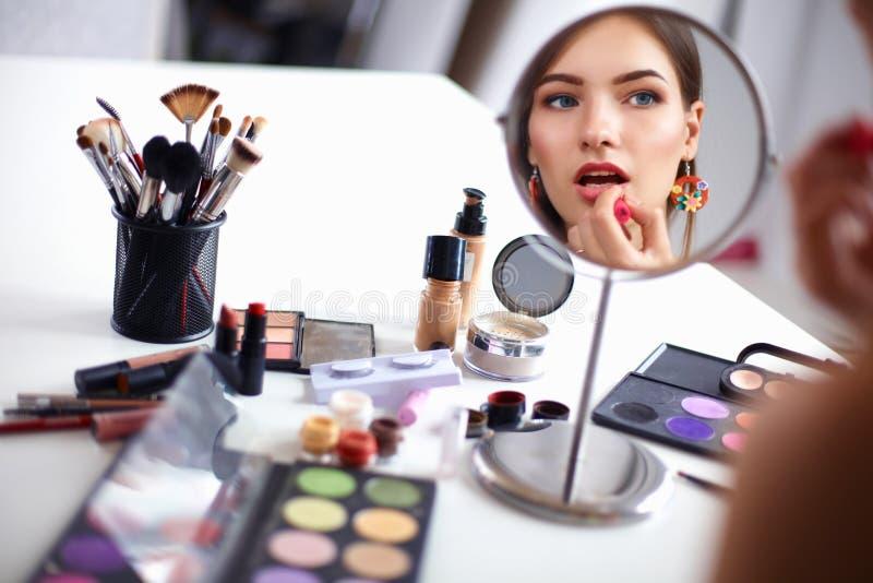 做构成的年轻美丽的妇女在镜子附近,坐在书桌 免版税库存图片