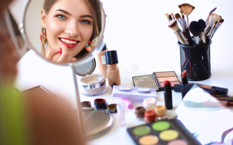 做构成的年轻美丽的妇女在镜子附近 库存图片