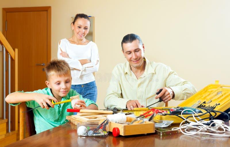 做某事与工具,父母的少年男孩是wat 免版税库存照片