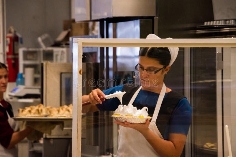 做柠檬蛋白甜饼的门诺派中的严紧派的妇女 图库摄影