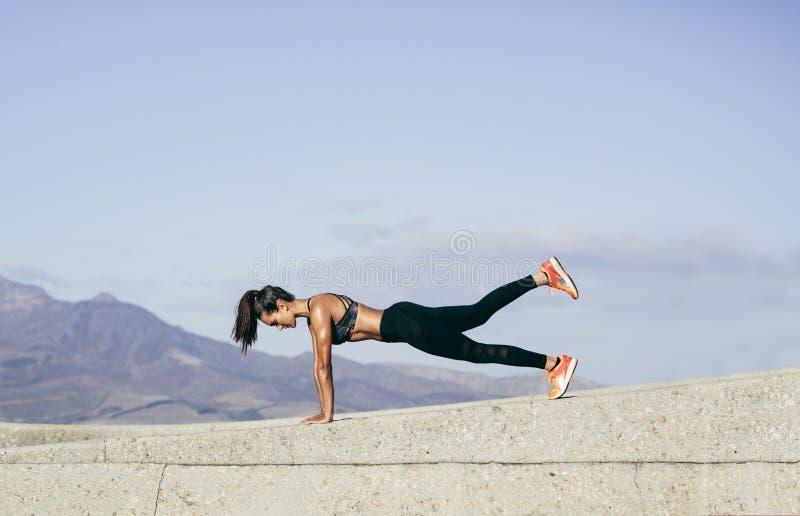 做核心锻炼的肌肉妇女户外 图库摄影