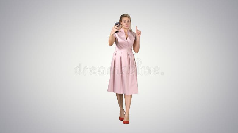 做桃红色的礼服的微笑的妇女打视频通话和走在梯度背景 库存照片