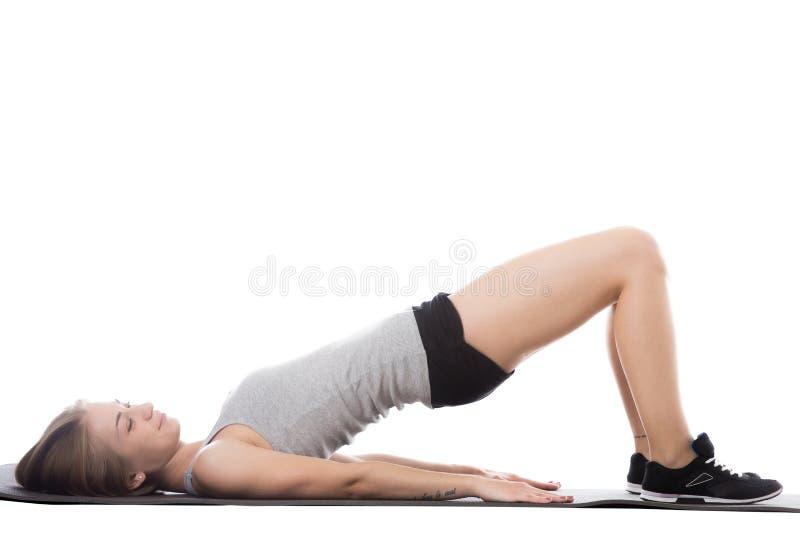 做桥梁锻炼的运动的妇女 库存照片