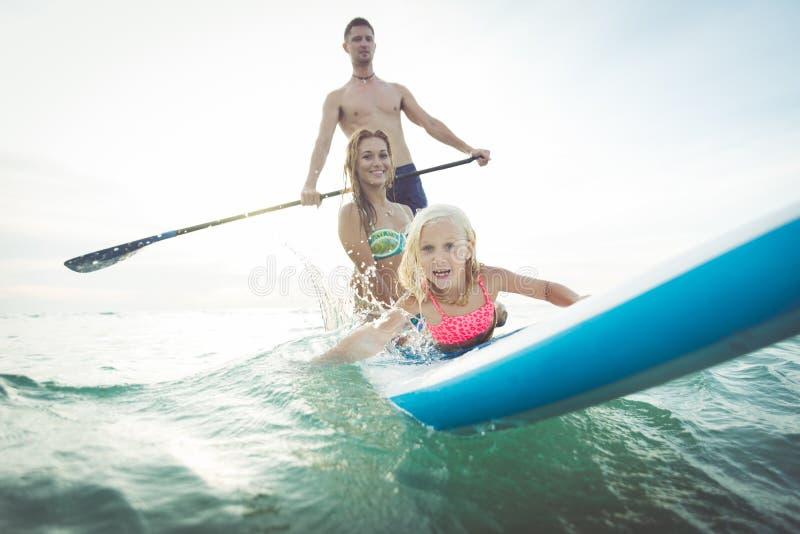 做桨海浪的家庭在海洋 库存照片