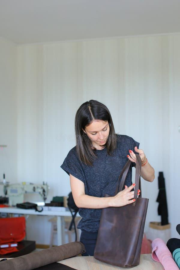 做棕色皮革手工制造袋子的创造性的妇女在工作室 图库摄影