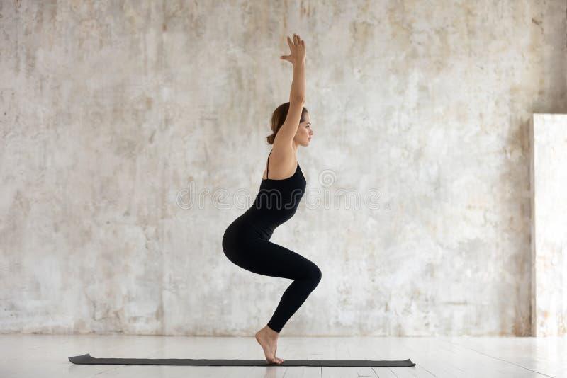 做椅子姿势Utkatasana瑜伽的侧视图妇女户内 免版税图库摄影