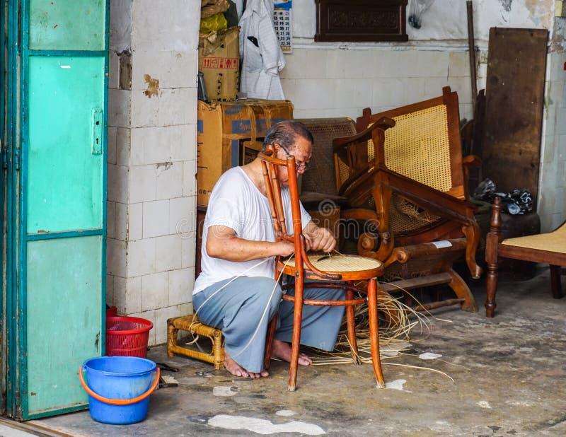做椅子的一个人在乔治城在槟榔岛,马来西亚 免版税库存图片