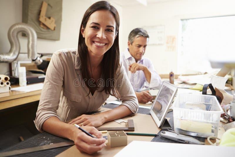做模型的两位建筑师在办公室使用数字式片剂 图库摄影