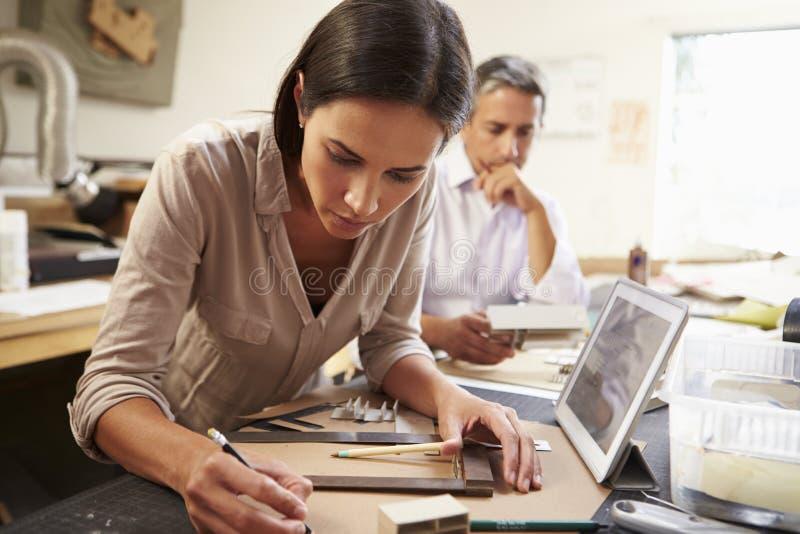 做模型的两位建筑师在办公室使用数字式片剂 库存照片