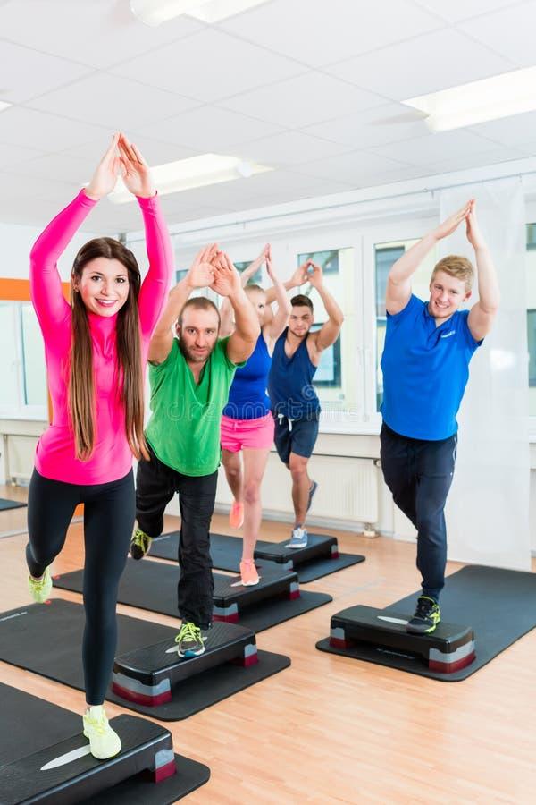 做步有氧运动的男人和妇女在健身房 免版税库存照片