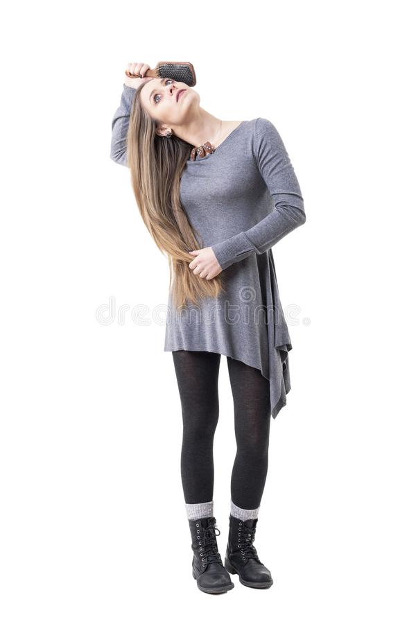 做每日惯例的轻松的年轻女人掠过她长的白肤金发的光滑的头发 库存图片