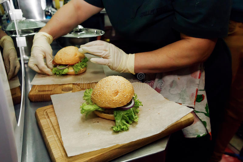 做汉堡的过程 在烹调汉堡包的手套的厨师手 免版税库存图片