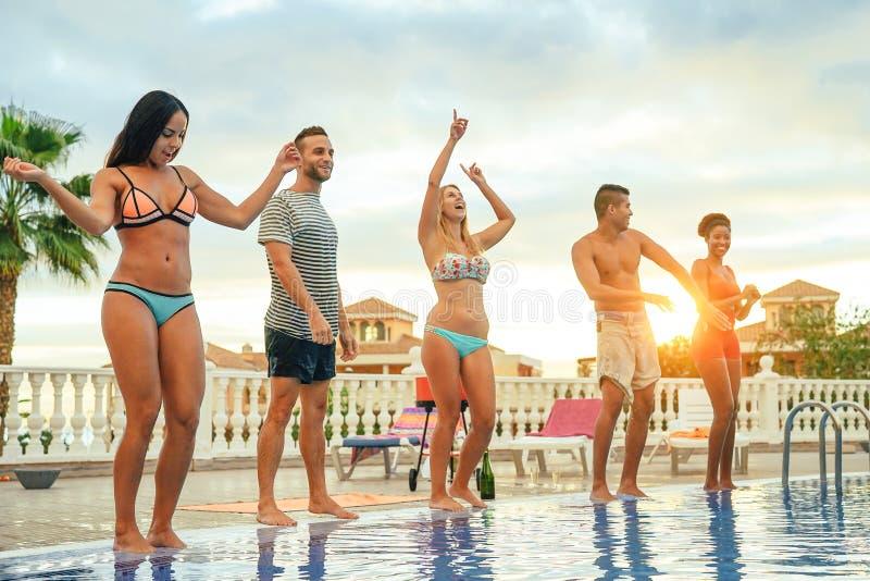 做池边聚会在日落-年轻人的小组愉快的朋友获得跳舞在水池旁边的乐趣 库存图片
