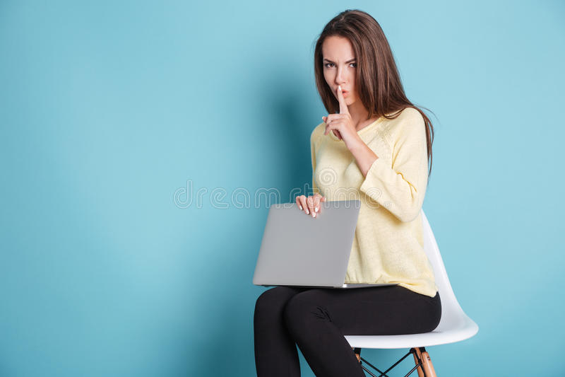 做沈默姿态的严肃的俏丽的妇女使用膝上型计算机 免版税库存照片