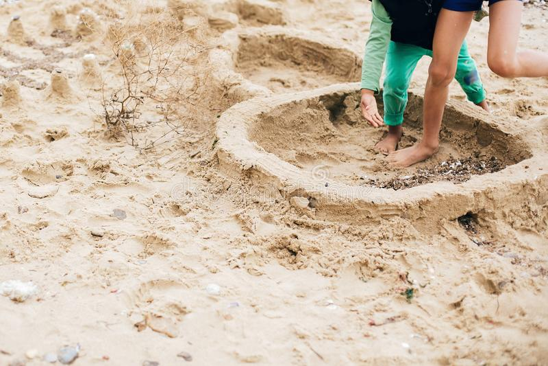 做沙子城堡的孩子在海滩 使用在沙子的幸福家庭和孩子,做墙壁沙堡在海附近 ?? 免版税库存图片