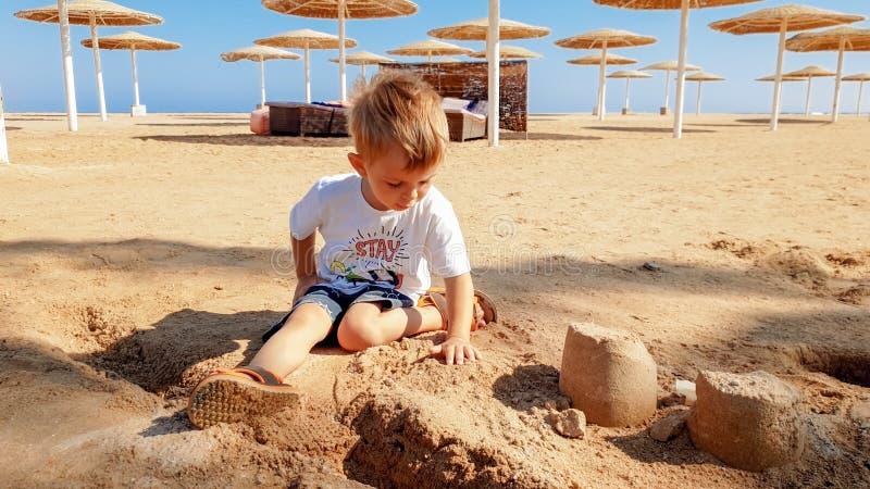 做沙子城堡的逗人喜爱的小男孩画象在海海滩 库存照片